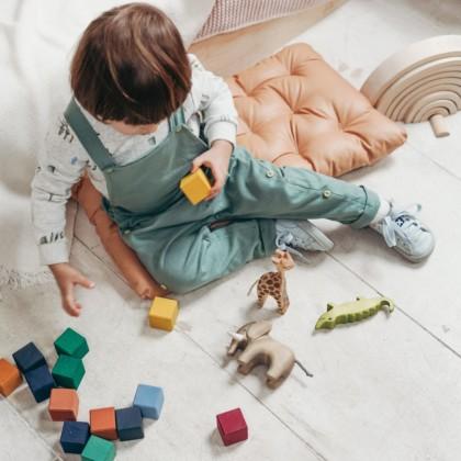 kind speelt op de grond met gekleurde blokken
