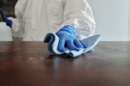 schoonmaker haalt doekje over een tafel